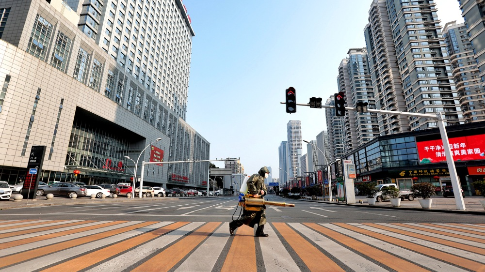 Worker with sanitising equipment crosses the road in front of a hospital in Yichang city of Hubei